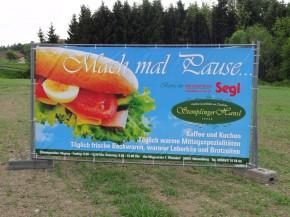 bedrucktes Werbebanner an Bauzaun